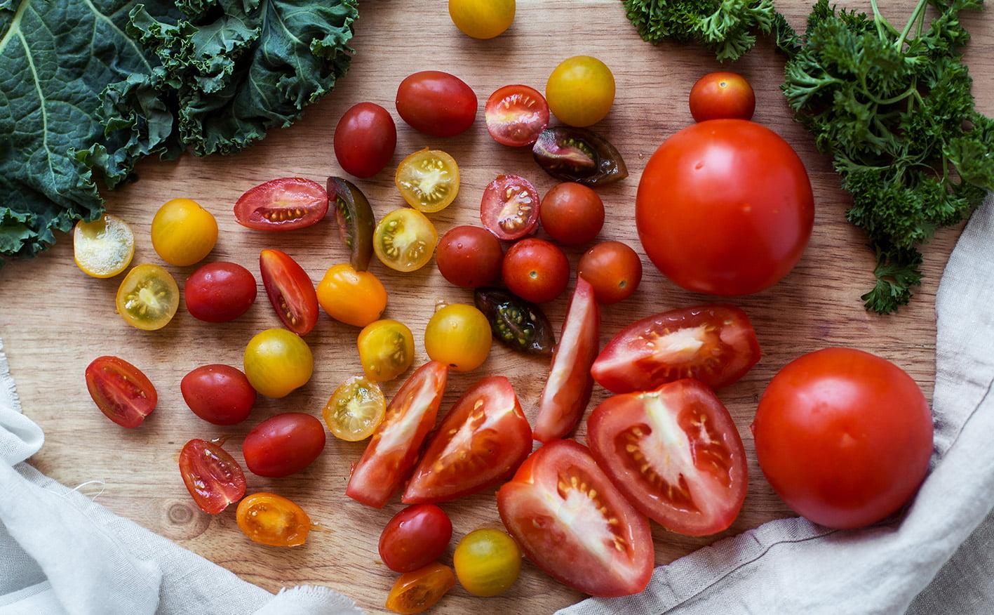 Kuvassa on puulaudalla erilaisia tomaatteja.