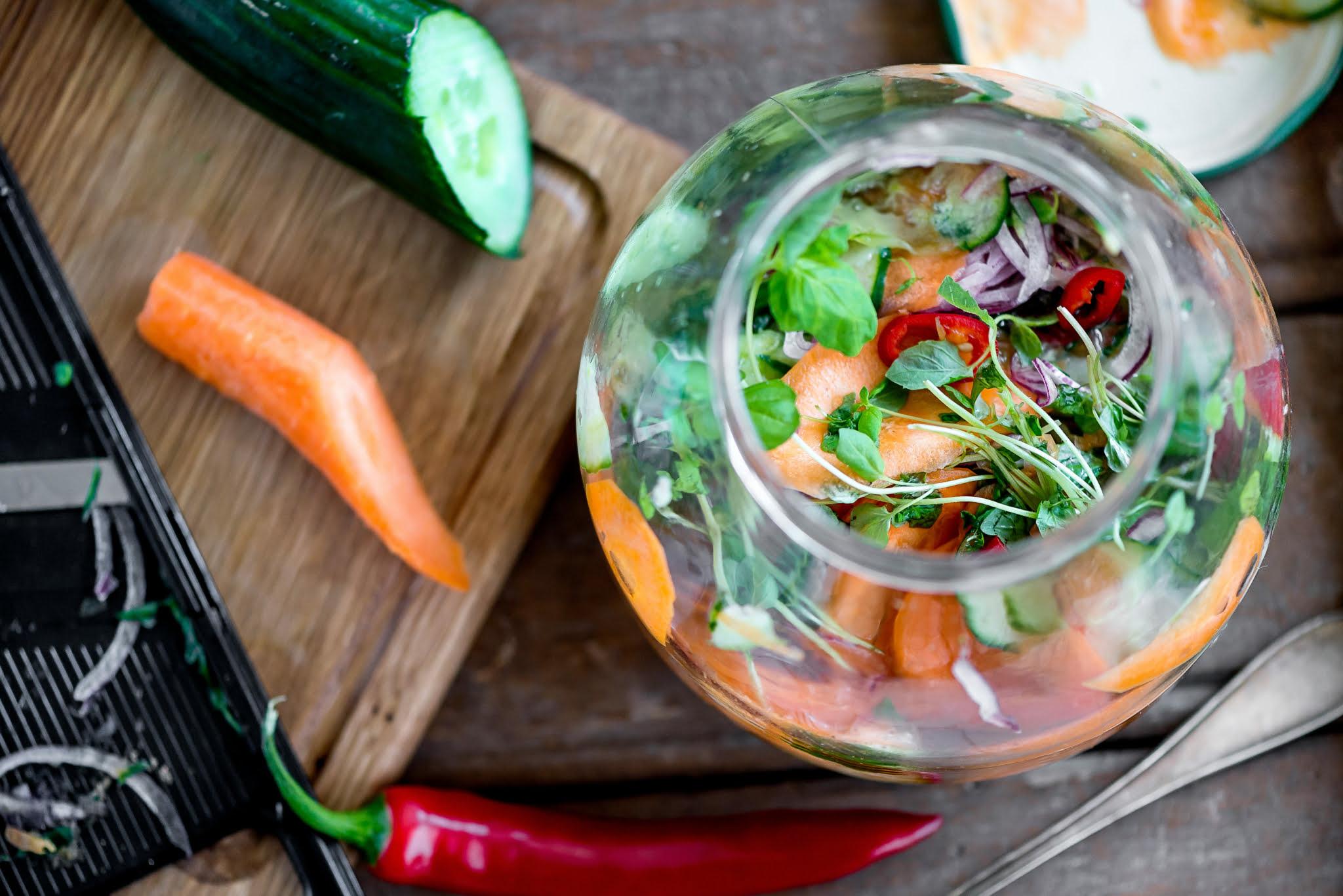 Kuvassa on kurkkurelissiä lasikipossa. Kipon vieressä on vihanneksia.