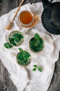 Kuvassa on valkoisella liinalla kolme kirkasta lasia täynnä minttuteetä. Liinalla on myös hunajapurkki ja teekannu. Liina on harmaalla puupöydällä.