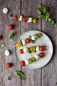 Kuvassa on kolme tomaatti-basilika-mozzarellatikkua harmaalla lautasella. Lautanen on harmaalla puupöydällä. Pöydällä on basilikaa, kirsikkatomaatteja ja basilikapalloja.